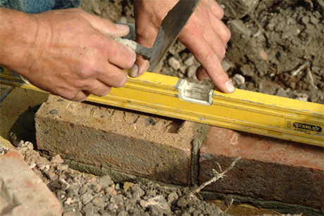 Man laying bricks with trowel and level
