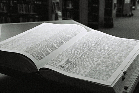 Black and white photo of open dictionary on a table in a library