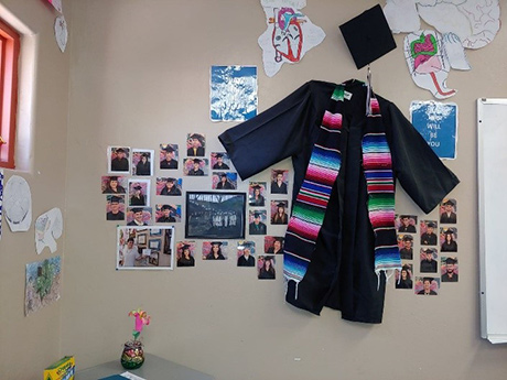 Graduation cap and gown stapled to the wall surrounded by pictures of students in their cap and gown
