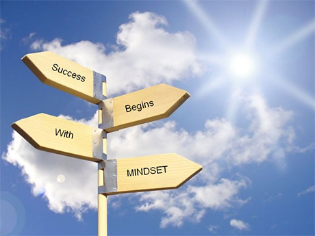 Signs pointing different directions with Success Begins With MINDSET against a blue sky with the sun