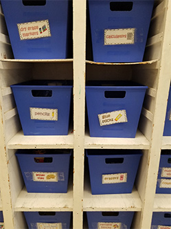 Labeled bins with cut-out handles on sectioned shelves that stand at the height of her students