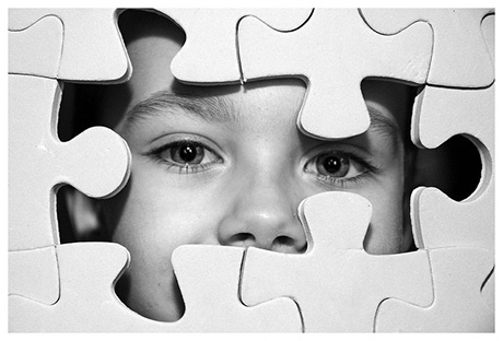 Puzzle with child's face looking out from behind it